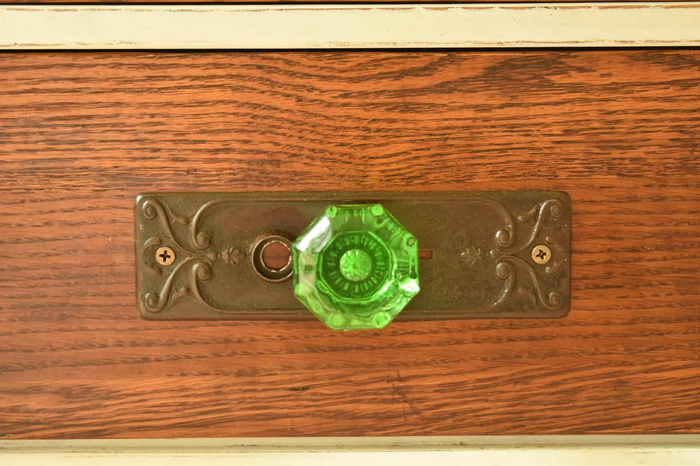 Emerald green glass doorknob on vintage furniture.