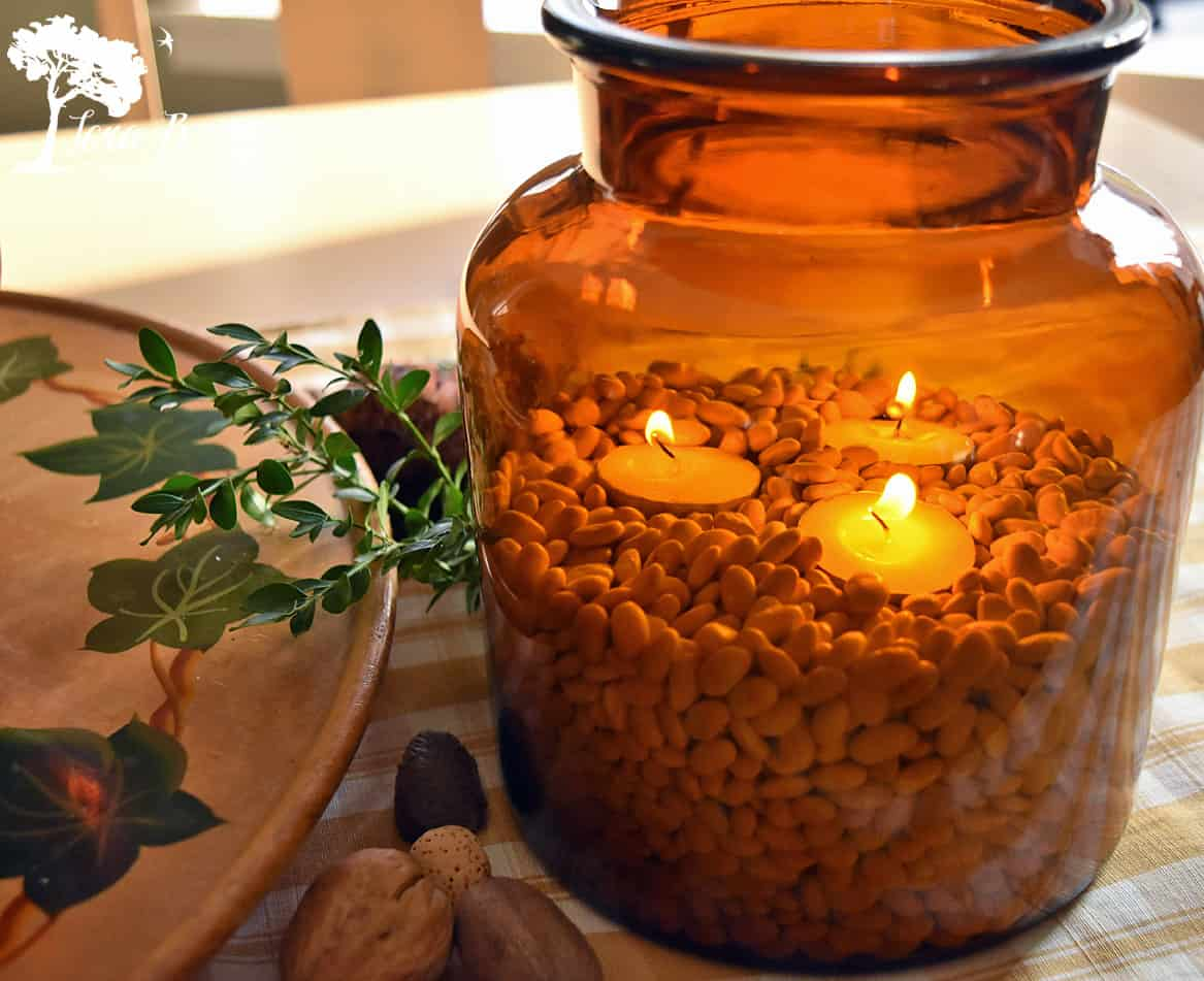 Candlelight glows from inside a brown glass vessel.