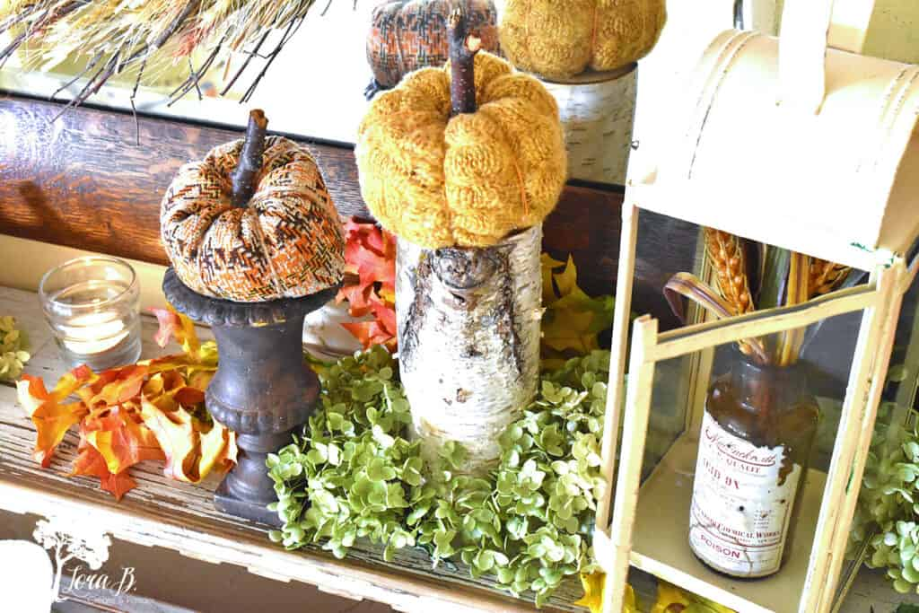 DIY fabric pumpkins and natural texures decorate the shelf in the decor of this Fall bedroom.