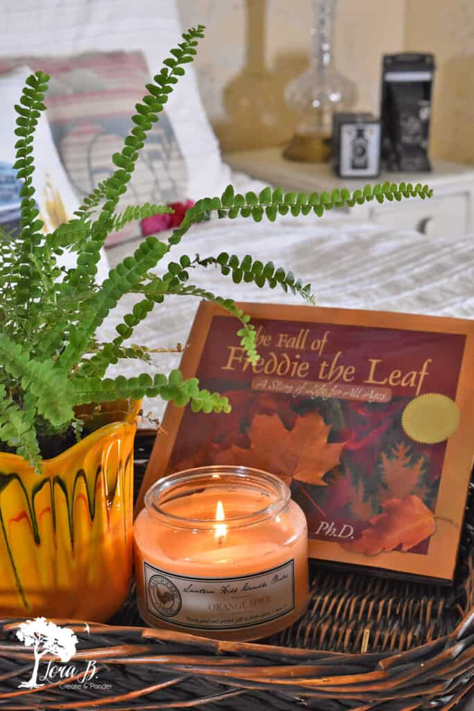 Wicker tray holds a candle, book and fern in this Fall decorated bedroom.