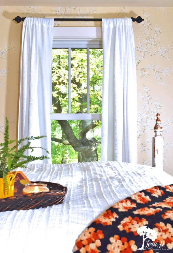 A black and orange vintage afghan brings a bolt of color to this Fall decorated bedroom.