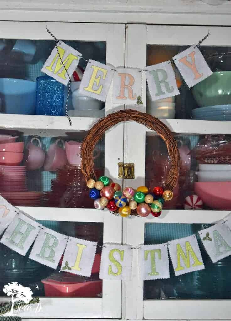 Drape garland or hang a wreath on the front of a glass front cabinet display for another idea.