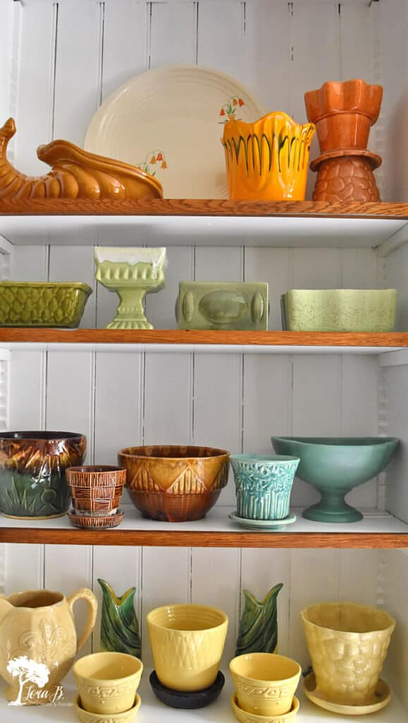 Vintage pottery collection creatively displayed by color.