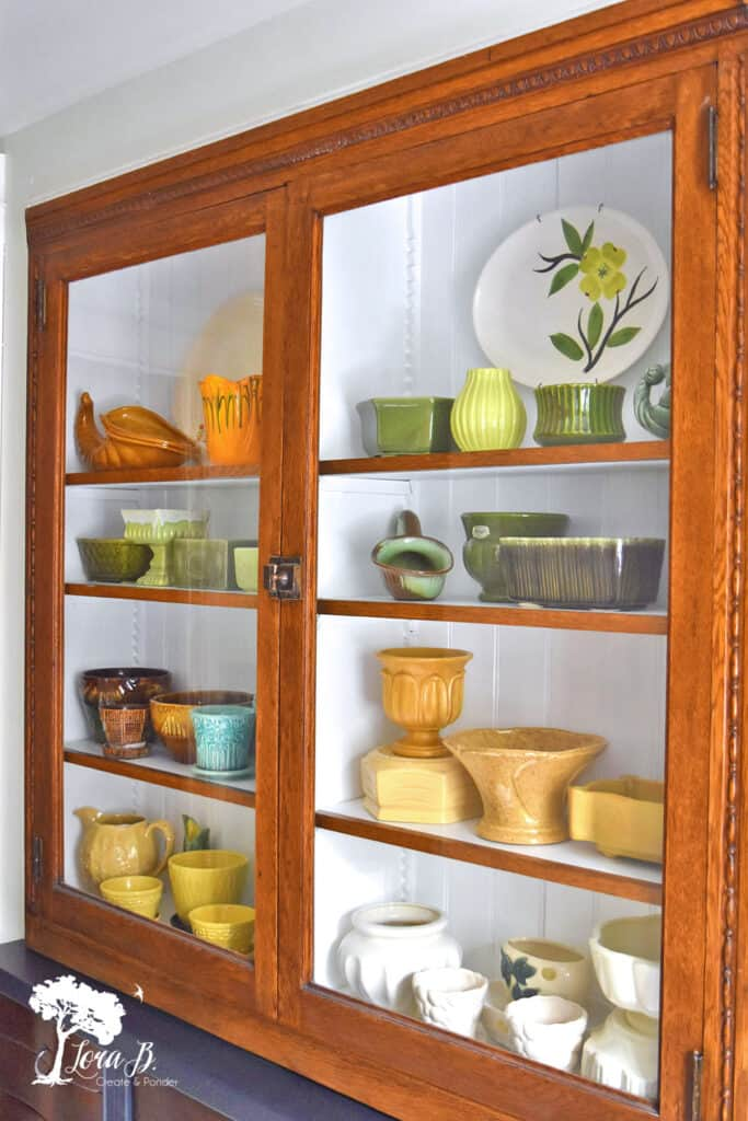 Built in cupboard displaying a collection of vintage pottery