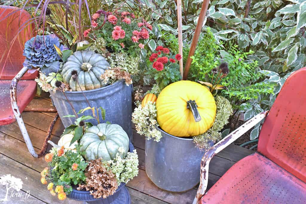 Repurposed metal garbage cans make beautiful outdoor planters on this Fall decorated porch and patio with salvaged style.