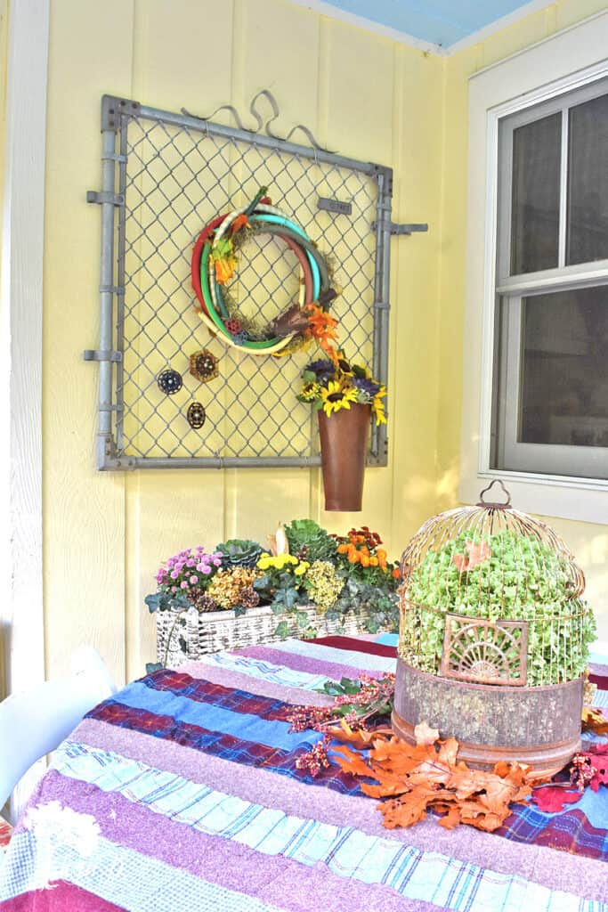 Old garden fence gate is cute with a hose wreath on this fall decorated porch and patio with salvaged style.