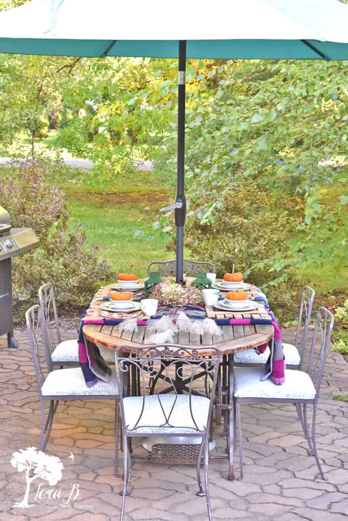 Vintage patchwork quilts and restaurant ware set the table on this Fall decorated porch and patio.