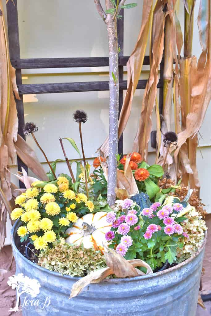 Repurposed metal trash can as outdoor planter on a fall decorated porch and patio tour with salvaged style.