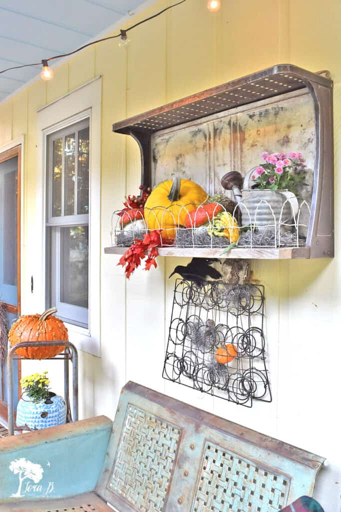 Repurposed vintage stovetop shelf decorated on a Fall porch.