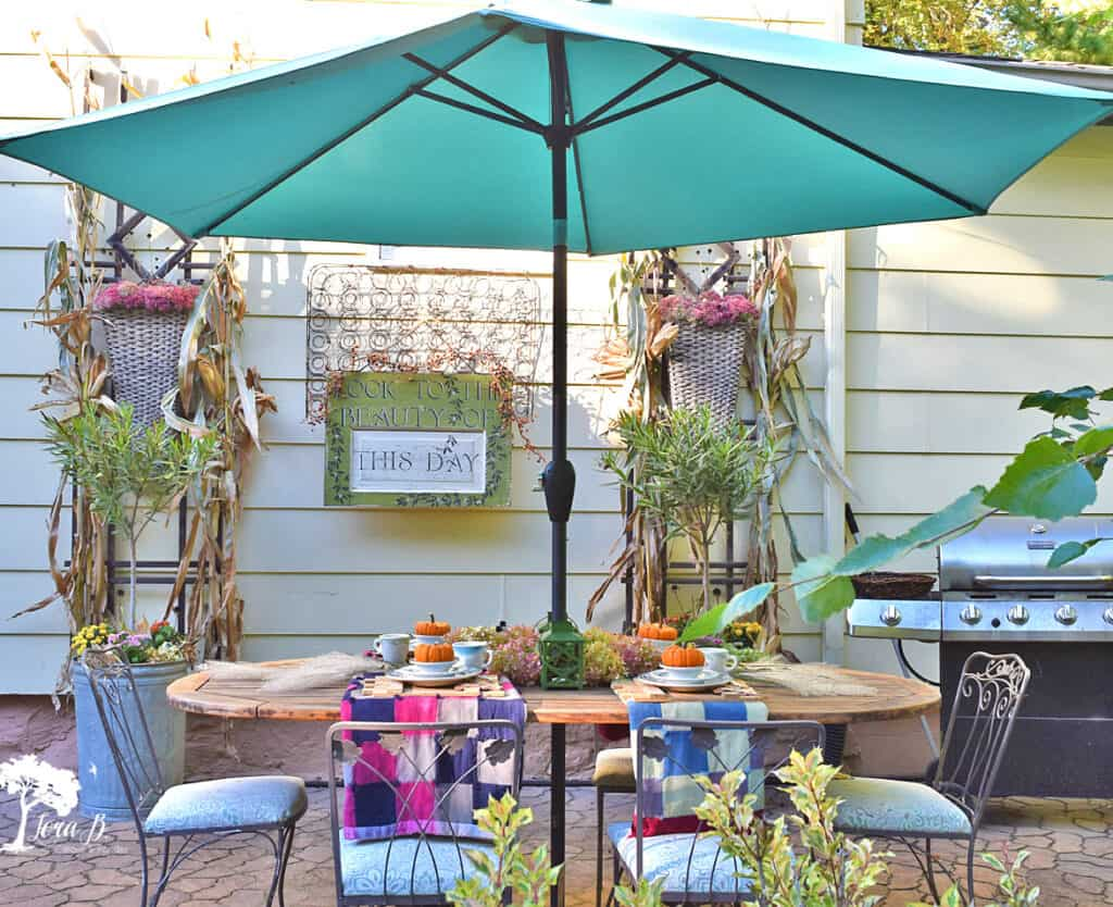 Vintage quilts set a table of vintage dishes on this Fall decorated porch and patio tour.