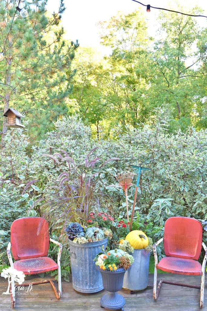 Vintage metal lawn chairs on a Fall decorated porch and patio with salvaged style.