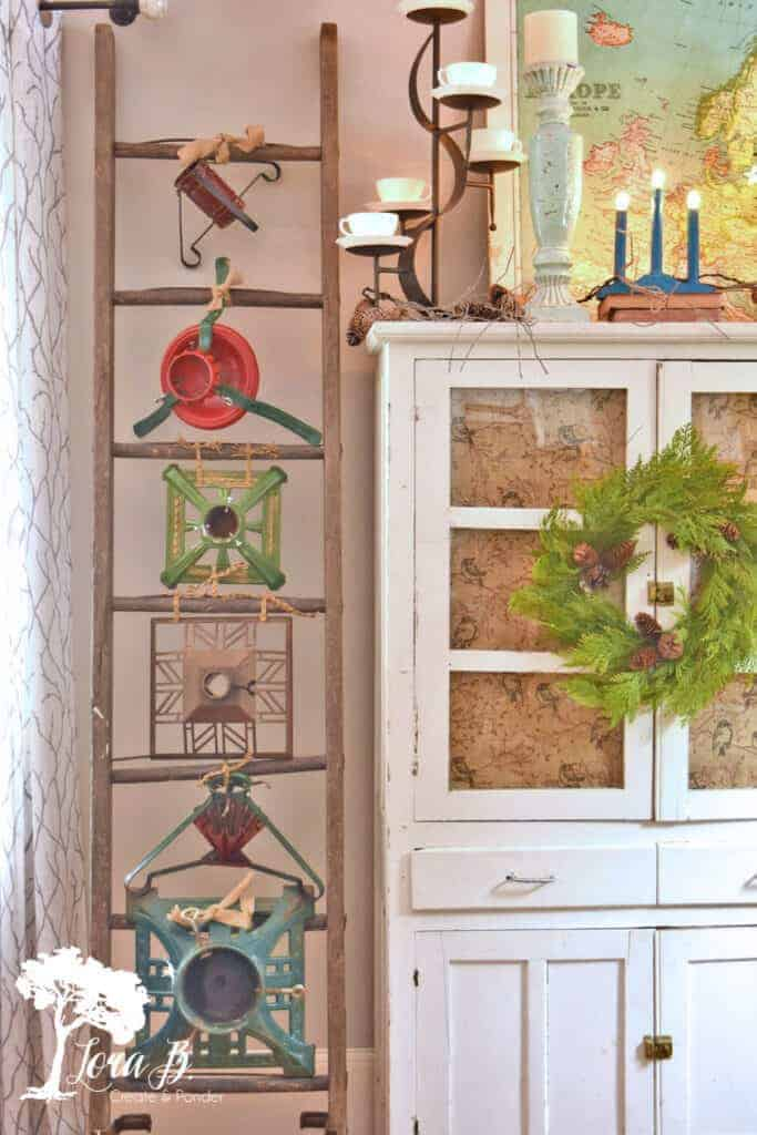 Glass front cabinet display ideas can include decorating the front with a wreath and the top with vintage accessories like this.