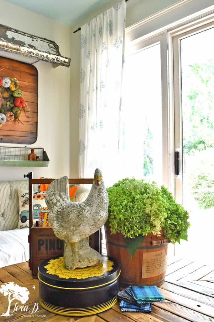An old wooden bucket, a repurposed old crate and a cement rooster decorate our coffee table; some recent vintage finds.